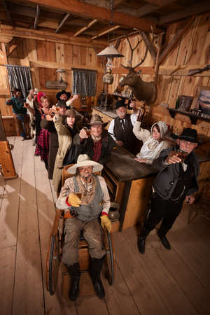 Large group of customers in old west saloon toasting with drinks