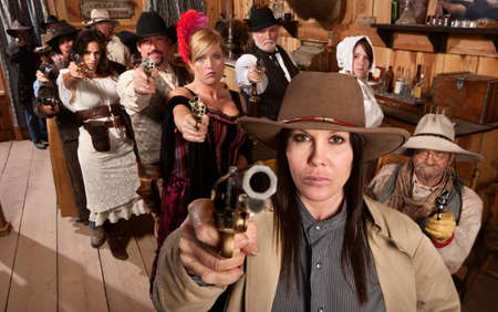 gunfighter: Armed saloon customers with pistols in old western scene