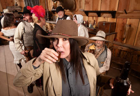 Cowgirl with bottle sipping whiskey from a shot glass Stock Photo - 13974816