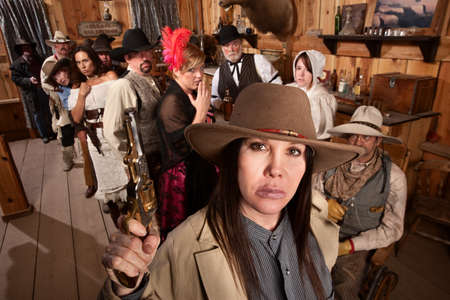 Dangerous woman with gun scares people in old west saloon photo