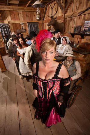 prostitute: Sexy show girl shows off with large crowd in old west saloon