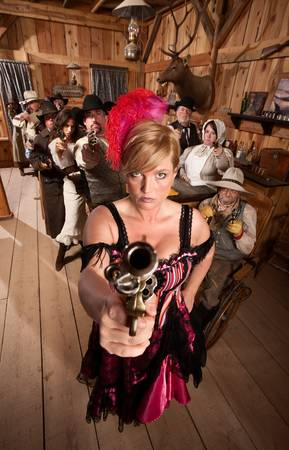 Show girl points her revolver in old west bar photo