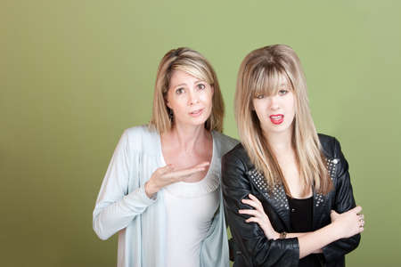 disobey: Frustrated mother and daughter over green background