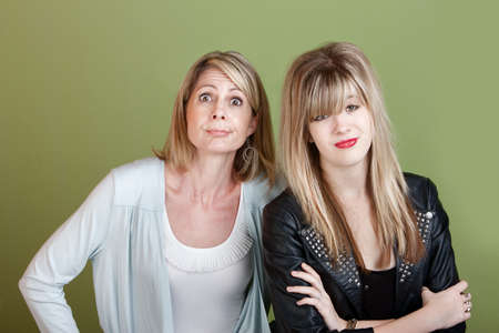 Caucasian mother and daughter over green background making faces photo