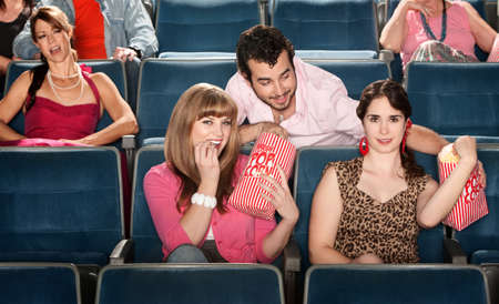 love movies: Smiling ladies sharing popcorn with man in theater