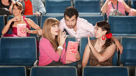 proposition: Flirtacious man with 2 young women in theater Stock Photo