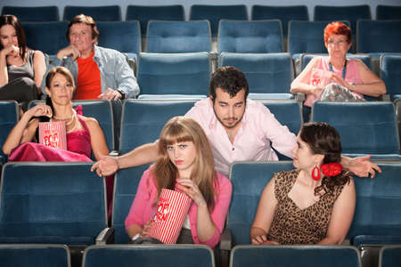 annoying: Rude bearded man talking to ladies in a theater