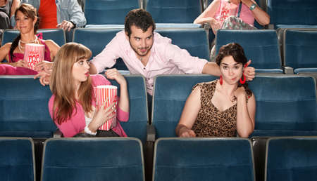 Shocked young women near flirting man in theater Stock Photo - 13974684