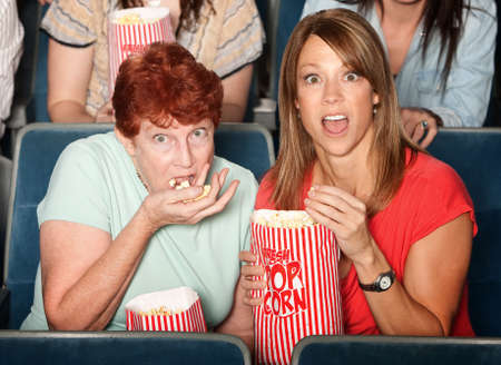 Scared Caucasian ladies in theater eating popcorn Stock Photo - 13974675