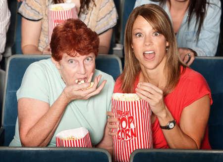 Scared Caucasian ladies in theater eating popcorn photo
