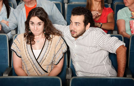 Guy in beard flirts with young woman in theater photo