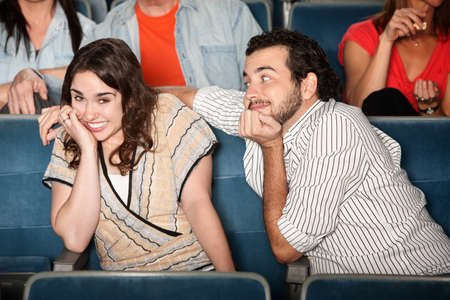 Embarressed young woman with flirting boyfriend in theater photo