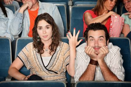 Frustrated woman with man staring at movie screen photo