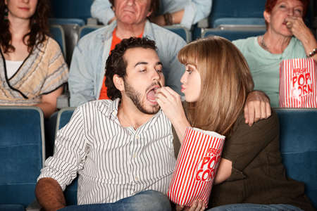 Loving young girlfriend feeds boyfriend popcorn in a theater photo