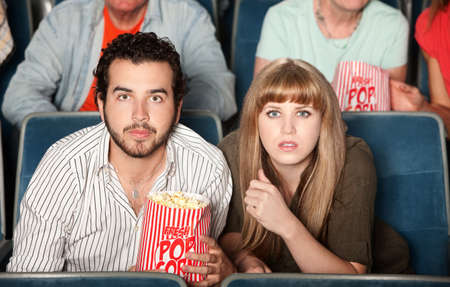suspense: Couple with popcorn bag staring ahead in a theater