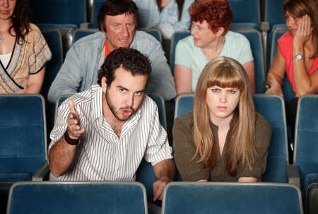 irked: Serious movie fans angry in a theater Stock Photo