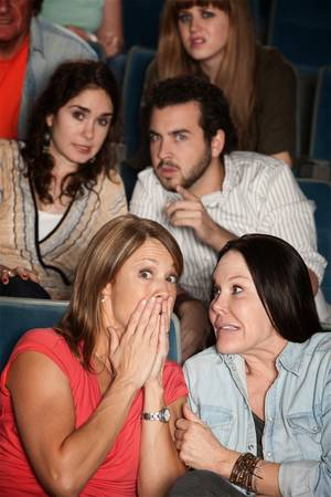 Group of scared men and women in a theater photo