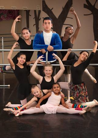Cute group of girls with male instructor at ballet class photo