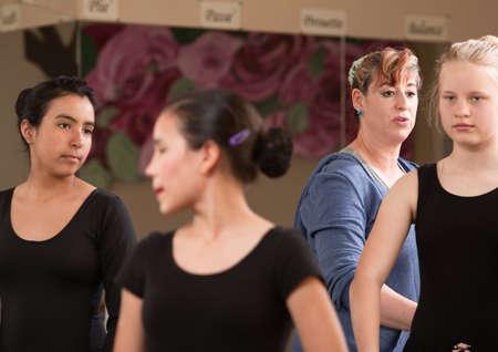 Ballet teacher behind students during dance practice