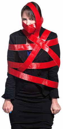 Angry female executive tied up in red tape