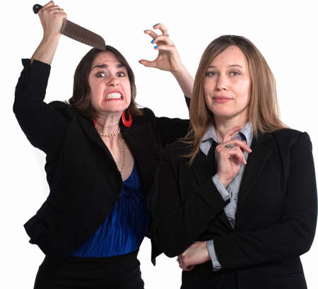 woman knife: Executive woman next to angry lady with knife in her hand Stock Photo