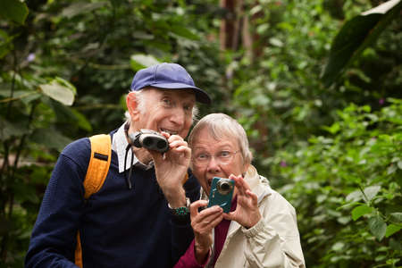 Two seniors with camera and binoculars in forest Stock Photo - 14022153