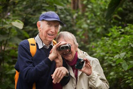 helps: Senior man helps wife look through binoculars in forest Stock Photo