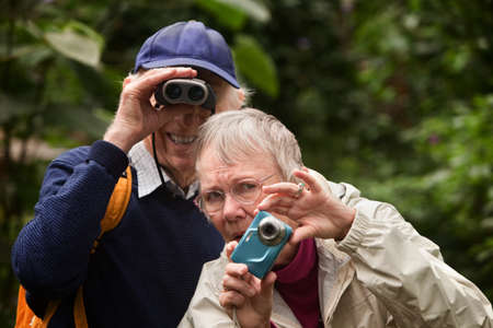 Concerned woman with camera and happy man with binoculars Stock Photo - 14022170