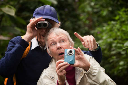 Man helps senior lady use camera in a forest Фото со стока