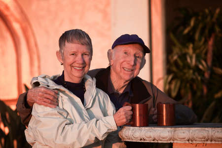 Smiling senior couple with coffee mugs in jackets photo