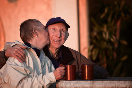 Senior woman kisses happy man in hat outdoors photo