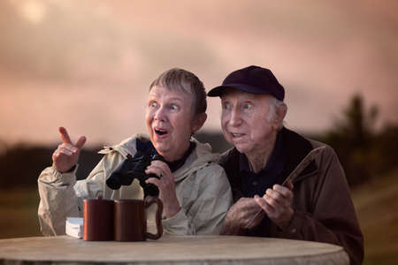 Happy senior bird watchers outside with binoculars photo