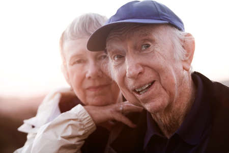citizen: Backlit happy senior man and woman outside Stock Photo