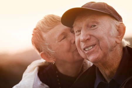 old couple: Happy man kissed by wife outside during sunset