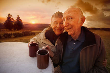Happy senior couple drinking coffee outside during sunset