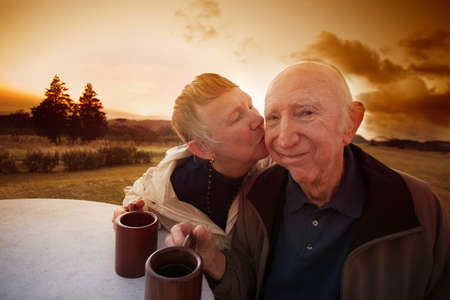 smooch: Senior man smirks while lady kisses him outside in field Stock Photo