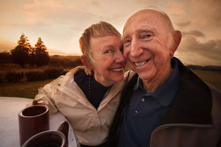 Close mature couple outside with coffee mugs photo