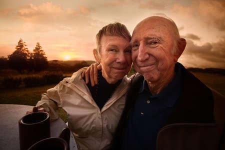 companionship: Dos personas mayores adultas que abarcan fuera en la mesa