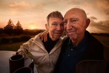 Two adult seniors embracing outside at table photo
