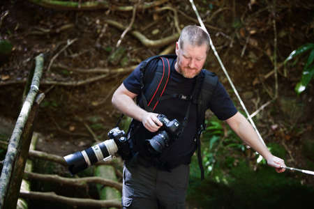Photographer with two cameras crossing a jungle rope bridge photo