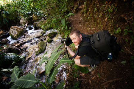 adventurer: Photographer looking back while sitting near a jungle brook Stock Photo