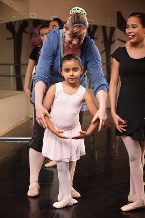 helps: Ballet class instructor helps young student with fourth position