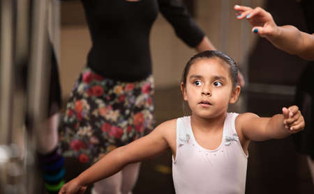 Cute little ballerina practicing in a dance studio photo