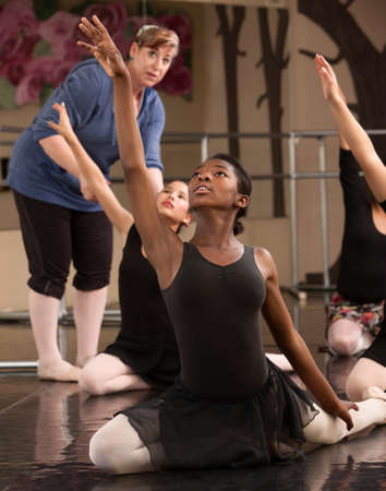 Ballet class teacher helps students practice dance moves photo