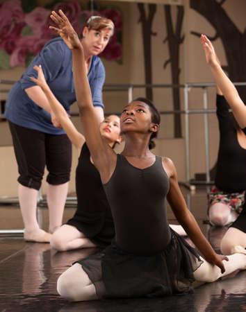 t�nzerin: Ballett Klassenlehrer hilft den Sch�lern Praxis Tanzbewegungen Lizenzfreie Bilder