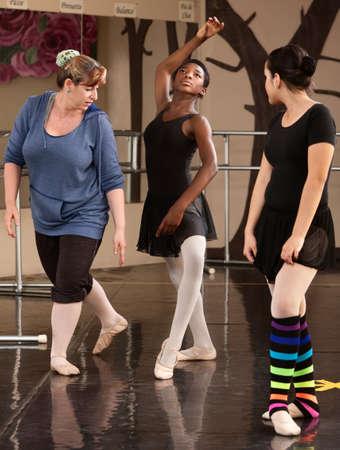 Dance teacher helps student in ballet class photo
