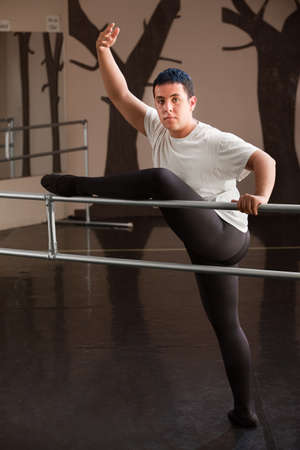 Young man displays a ballet dance pose on railing photo