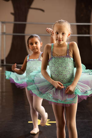Two children in ballet dresses standing in a dance studio photo