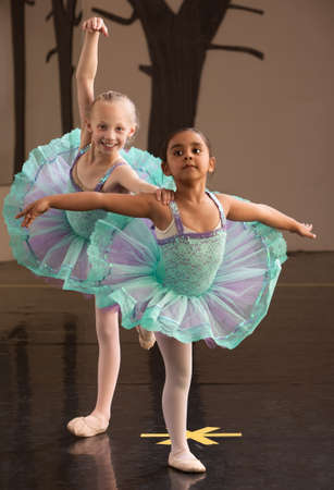 Two ballet students in fancy dresses posing together