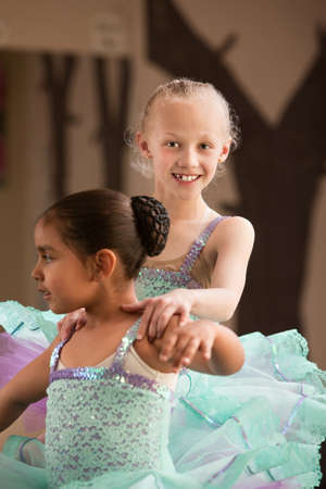 Cute child ballet student helps her partner during rehearsal photo